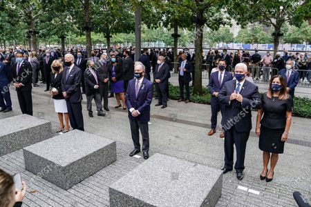 From left, New York Gov. Andrew Cuomo, Democratic presidential candidate and former Vice President Joe Biden, former New York Mayor Mike Bloomberg, and Vice President Mike Pence stand during the national anthem at the National September 11 Memorial and Museum, in New York. Americans will commemorate 9/11 with tributes that have been altered by coronavirus precautions and woven into the presidential campaign