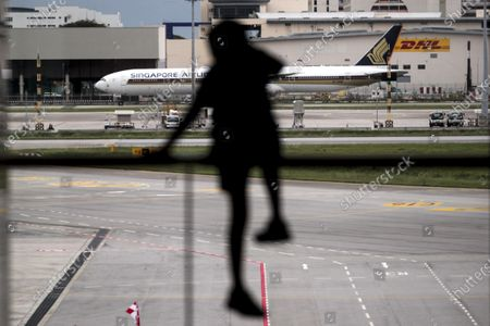 A child climbing a railing is silhouetted against a Singapore Airlines B777 parked at the Changi Airport in Singapore, 11 September 2020. Singapore Airlines (SIA) has announced that it will cut 2400 staff members affecting pilots, cabin crew, and ground staff, in the wake of the economic fallout from the Covid-19 coronavirus pandemic which saw the flag carrier report losses of over 1 billion SGD in the first quarter of 2020.