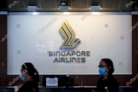 Stock Picture of Two women walk past the Singapore Airlines logo above an information counter at the departure hall of the Changi Airport in Singapore, 11 September 2020. Singapore Airlines (SIA) has announced that it will cut 2400 staff members affecting pilots, cabin crew, and ground staff, in the wake of the economic fallout from the Covid-19 coronavirus pandemic which saw the flag carrier report losses of over 1 billion SGD in the first quarter of 2020.