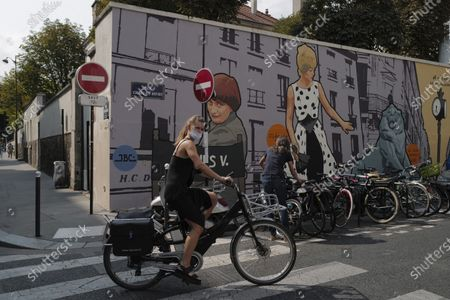 Stock Photo of Woman, wearing a protective face mask as a precaution against the coronavirus, rides her bicycle front of a mural representing late film director Agnes Varda, in Paris, . French health authorities have reported on Thursday 9,843 infections from the coronavirus in 24 hours, the highest daily tally since the end of France's lockdown in April. France has seen a sharp uptick in new cases in recent weeks and hospitalizations have started to increase steadily, reaching now over 5,000 including 615 people in ICU