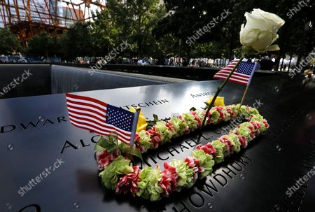 Flowers and US flags adorn the name of perished New York City firefighter Michael Collins at the south tower reflecting pool at the 19th anniversary commemoration ceremony of the 11 September 2001 terrorist attack on the World Trade Center in New York, USA, 11 September 2020.