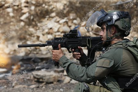 Israeli soldier fires rubber bullets at Palestinian protesters during a demonstration against Israel's settlements in the village of Kofr Qadom near the northern West Bank city of Nablus, 11 September 2020.