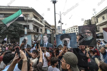 Syrians holds posters during a demonstration against President Bashar al-Assad in Idlib city
