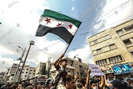 Syrians raising flag during a demonstration against President Bashar al-Assad in Idlib city