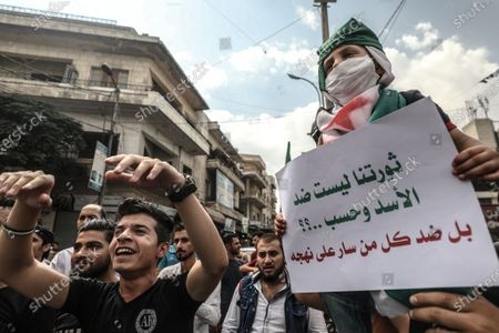 Syrians holds placards during a demonstration against President Bashar al-Assad in Idlib city