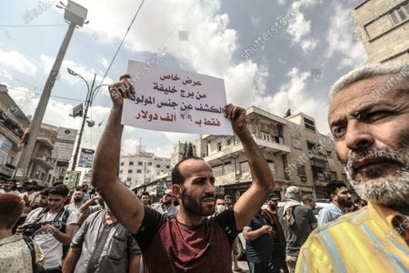 A Syrians holds placards during a demonstration against President Bashar al-Assad in Idlib city