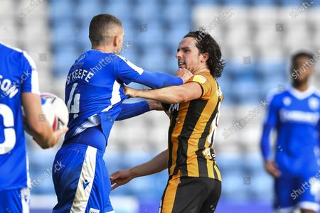 George Honeyman of Hull City and Stuart O'Keefe of Gillingham clash after a foul on Mallik Wilks of Hull City