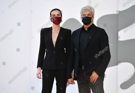Italian Polish-born actress Kasia Smutniak (L) and Italian film producer Domenico Procacci wear protective face mask as they arrive for the premiere of 'I Predatori' during the 77th annual Venice International Film Festival, in Venice, Italy, 11 September 2020. The movie is presented in the Orizzonti section at the festival running from 02 September to 12 September. The event is the first major in-person film fest to be held in the wake of the Covid-19 coronavirus pandemic. Attendees have to follow strict safety measures like mandatory face masks indoors, temperature scanners, and socially distanced screenings to reduce the risk of infection. The public is barred from the red carpet, and big stars are expected to be largely absent this year.