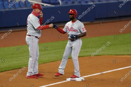 Philadelphia Phillies' Andrew McCutchen (22) is congratulated by third base coach Dusty Wathan after advancing on a balk by Miami Marlins starting pitcher Trevor Rogers during the first inning of a baseball game, in Miami