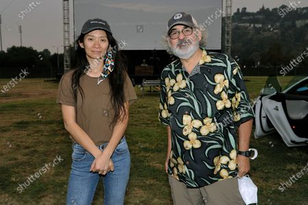 "Chloe Zhao, left, and Stephen Gilula attend the Telluride from Los Angeles drive-in screening of ""Nomadland"", at the Rose Bowl in Pasadena, Calif"