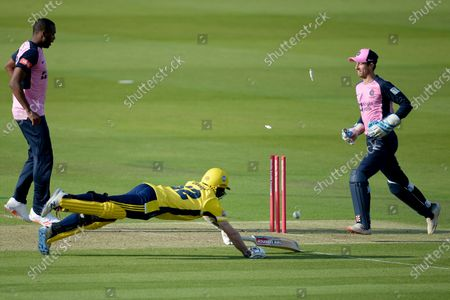 Mason Crane of Hampshire dives full stretched but can't prevent himself being run out by John Simpson