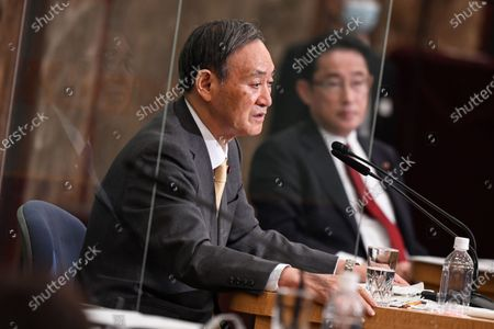 Japan's Liberal Democratic Party's leadership election candidates, former Japan's defence minister Shigeru Ishiba (left on the reflection), Japan's Chief Cabinet Secretary Yoshihide Suga (center) and Japan's former foreign minister Fumio Kishida (right) attend a debate ahead of the Liberal Democratic Party's (LDP) leadership election