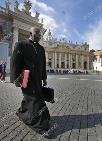 "Cardinal Robert Sarah, of Guinea, walks in St. Peter's Square after attending a cardinals' meeting, at the Vatican. The Vatican said Saturday it was ""necessary and urgent"" to return to in-person Masses as soon as coronavirus lockdowns permit"