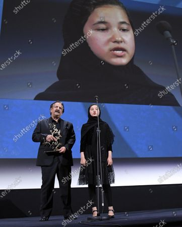 """Iranian director Majid Majidi (L) and Iranian actress Shamila Shirzad receive on behalf of Iranian actor Rouhollah Zamani the Special Jury Prize Marcello Mastroianni Award for Best New Young Actor for """"Khorshid"""" (Sun Children) during the Winners' Photocall on the last day of the 77th Venice Film Festival, in Venice, Italy, 12 September 2020. The event is the first major in-person film fest to be held in the wake of the Covid-19 coronavirus pandemic. Attendees had to follow strict safety measures like mandatory face masks indoors, temperature scanners, and socially distanced screenings to reduce the risk of infection. The public was barred from the red carpet, and big stars were largely absent this year. The 77th edition of the festival runs from 02 to 12 September 2020."""