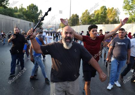 Anti-government protesters shout slogans during a protest against the Lebanese President Michel Aoun near the presidential palace, in Baabda east of Beirut, Lebanon, . Lebanese soldiers on Saturday fired rubber bullets and live rounds in the air to disperse hundreds of protesters trying to march to the presidential palace during an anti-government demonstration
