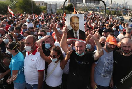 Supporters of Lebanese President Michel Aoun gather near the Presidential palace to support him against the anti-government protesters, in Baabda east of Beirut, Lebanon, . Lebanese soldiers on Saturday fired rubber bullets and live rounds in the air to disperse hundreds of protesters trying to march to the presidential palace during an anti-government demonstration
