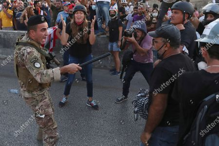 Lebanese army soldier shouts as he tries to push back the anti-government protesters, during a protest against the Lebanese President Michel Aoun near the presidential palace, in Baabda east of Beirut, Lebanon, . Soldiers fired rubber bullets and live rounds in the air to disperse hundreds of protesters trying to march to the presidential palace during an anti-government demonstration