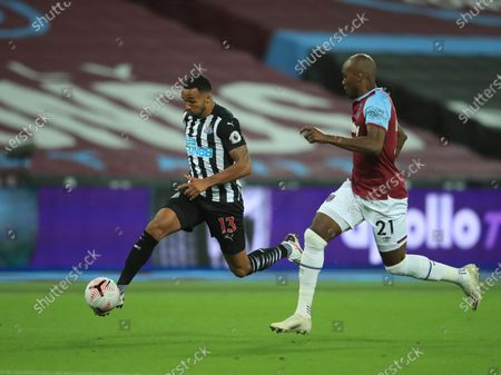 Newcastle's Callum Wilson, left, duels for the ball with West Ham's Angelo Ogbonna during the English Premier League soccer match between West Ham United and Newcastle United at the London Stadium in London