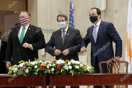 Secretary of State Mike Pompeo, left, Cypriot President Nicos Anastasiades, center, and Cypriot Foreign Minister Nikos Christodoulides touch elbows during their meeting at the Presidential Palace in Nicosia, Cyprus, . Pompeo's lightning visit to Cyprus aimed to de-escalate a confrontation between Greece and Turkey over energy reserves in east Mediterranean waters and to affirm Washington's continued engagement in the tumultuous region four days after Russian Foreign Minister Sergey Lavrov pitched Moscow's offer to help ease tensions during his trip to the island nation