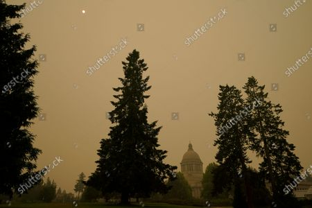 Stock Image of Smoke from wildfires in Oregon and California creates hazy skies as the sun is seen above the Washington state Capitol, Saturday afternoon, in Olympia, Wash. Numerous air quality warnings were in place for most of the West through the weekend