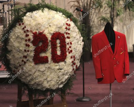 Red jacket belonging to St. Louis Cardinals legend Lou Brock hangs near a floral wreath with Brock's retired number 20 during the funeral service for the baseball Hall of Famer, at Greater Grace Church in Ferguson, Mo. Brock, the dynamic leadoff hitter and base stealer who helped the St. Louis Cardinals win three pennants and two World Series, died Sunday, Sept. 6, 2020 at age 81