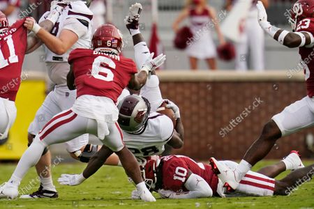 Missouri State wide receiver Kevon Latulas (28) is upended by Oklahoma defensive back Pat Fields (10) in front of Oklahoma's Tre Brown (6) in the first half of an NCAA college football game, in Norman, Okla