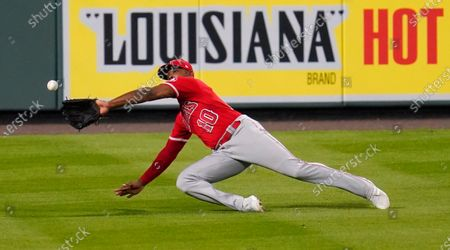 Los Angeles Angels left fielder Justin Upton reaches out to snare a line drive hit by Colorado Rockies' Daniel Murphy during the eighth inning of a baseball game, in Denver. The Angels won 5-2 in 11 innings