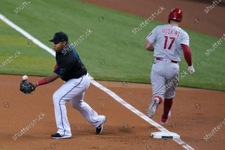 Miami Marlins first baseman Jesus Aguilar, left, is unable catch the throw in time to tag out Philadelphia Phillies' Rhys Hoskins (17) on a fielding error by third baseman Brian Anderson during the first inning of a baseball game, in Miami