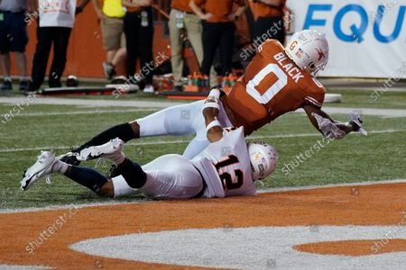 Texas' Tarik Black (0) dives into the end zone for a touchdown as UTEP's Dennis Barnes (12) defends during the first half of an NCAA college football game in Austin, Texas