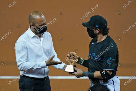 Stock Photo of Miami Marlins CEO Derek Jeter, left, presents Miami Marlins shortstop Miguel Rojas a trophy for being chosen as the Marlins' nominee for the Roberto Clemente Award, during a ceremony before the start of a baseball game between the Marlins and the Philadelphia Phillies, in Miami