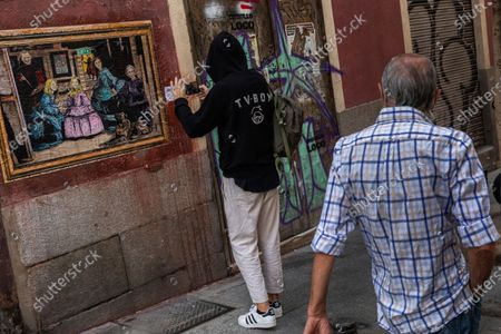 """Artist TVBOY takes a snapshot of his painting named """"Las Meninas 2.0"""", depicting the Spanish royal family dressed like """"Las Meninas"""" by Diego Velazquez in Madrid, Spain, . Former monarch Juan Carlos is the target of official investigations in Spain and Switzerland, into possible financial wrongdoing"""