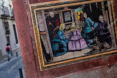 """Woman walks past a painting named """"Las Meninas 2.0"""" by artist TVBOY depicting the Spanish royal family dressed like """"Las Meninas"""" by Diego Velazquez in Madrid, Spain, . Former monarch Juan Carlos is the target of official investigations in Spain and Switzerland, into possible financial wrongdoing"""