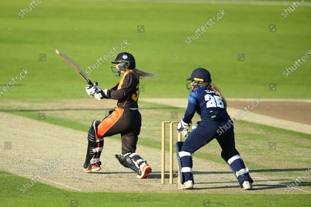 Stock Image of Chloe Hill of Central Sparks hits the winning runs as Bess Heath of Northern Diamonds looks on.