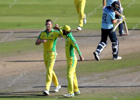 Australia's Josh Hazlewood, left, celebrates the dismissal of England's Chris Woakes, right, during the second ODI cricket match between England and Australia, at Old Trafford in Manchester, England