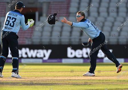 England's captain Eoin Morgan, right, throws the helmet towards wicketkeeper Jos Buttler during the second ODI cricket match between England and Australia, at Old Trafford in Manchester, England