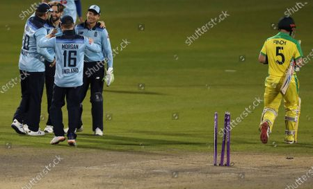England's Chris Woakes, second left, is congratulated by teammates after dismissing Australia's captain Aaron Finch, right, during the second ODI cricket match between England and Australia, at Old Trafford in Manchester, England