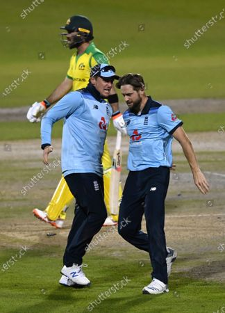 England's Chris Woakes, right, celebrates the dismissal of Australia's Glenn Maxwell, rear, during the second ODI cricket match between England and Australia, at Old Trafford in Manchester, England