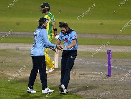 England's Chris Woakes, right, celebrates with teammate Jason Roy the dismissal of Australia's Glenn Maxwell, center, during the second ODI cricket match between England and Australia, at Old Trafford in Manchester, England