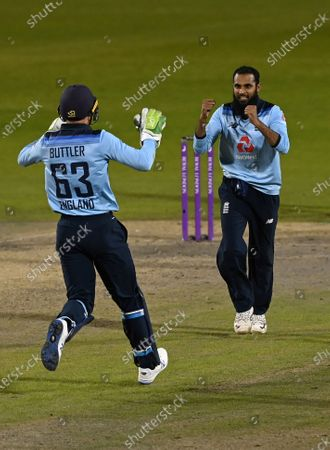 England's Adil Rashid, right, celebrates with teammate Jos Buttler after taking the wicket of Australia's Alex Carey to win the second ODI cricket match between England and Australia, at Old Trafford in Manchester, England