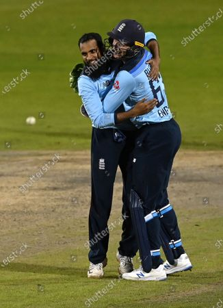 England's Adil Rashid, left, celebrates with teammate Jos Buttler after taking the wicket of Australia's Alex Carey to win the second ODI cricket match between England and Australia, at Old Trafford in Manchester, England