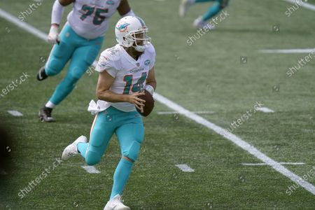 Miami Dolphins quarterback Ryan Fitzpatrick rolls out to pass against the New England Patriots in the first half of an NFL football game, in Foxborough, Mass