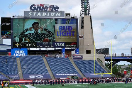 """New England Patriots stand during the singing of """"Lift Every Voice and Sing"""" by Alicia Keys, on the video screen, before an NFL football game against the Miami Dolphins, in Foxborough, Mass"""