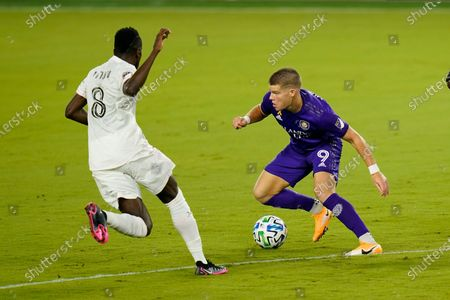 Stock Photo of Orlando City's Chris Mueller (9) makes a move to get past Inter Miami's Blaise Matuidi (8) during the first half of an MLS soccer match, in Orlando, Fla