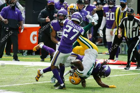 Green Bay Packers wide receiver Davante Adams, center, is upended by Minnesota Vikings cornerback Cameron Dantzler (27) and defensive back Anthony Harris, right, during the first half of an NFL football game, in Minneapolis