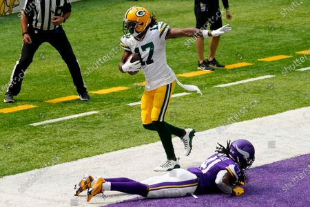 Green Bay Packers wide receiver Davante Adams (17) catches a 24-yard touchdown pass over Minnesota Vikings defensive back Anthony Harris during the first half of an NFL football game, in Minneapolis