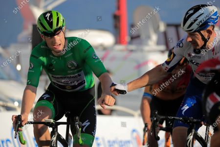 Ireland's Sam Bennett, wearing the best sprinter's green jersey, thanked teammate Denmark's Michael Morkov, right, who set the pace for him on the last climb of stage 15 of the Tour de France cycling race over 174.5 kilometers (108.4 miles) from Lyon to Grand Colombier pass, France