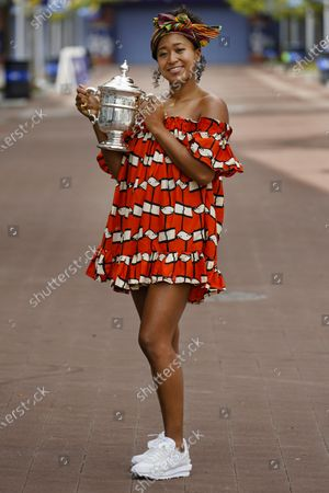Stock Image of Naomi Osaka, of Japan, holds up the championship trophy while posing for photographs at the Billie Jean King National Tennis Center, in New York