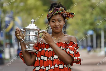 Stock Picture of Naomi Osaka, of Japan, holds up the championship trophy while posing for photographs at the Billie Jean King National Tennis Center, in New York