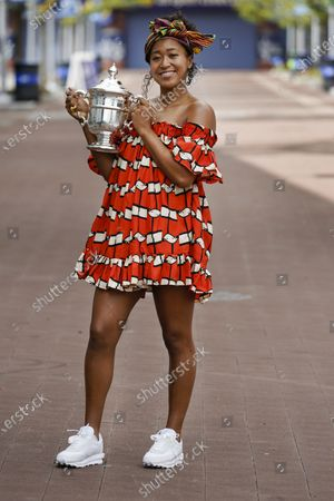 Naomi Osaka, of Japan, holds up the championship trophy while posing for photographs at the Billie Jean King National Tennis Center, in New York