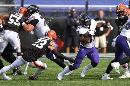 Stock Picture of Baltimore Ravens running back Gus Edwards (35) runs the ball against Cleveland Browns safety Andrew Sendejo (23) in the second half during an NFL football game, in Baltimore